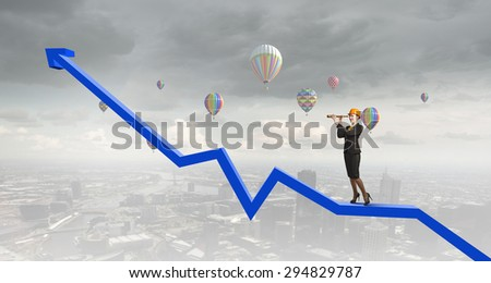 Young woman engineer on graph and looking in spyglass - stock photo