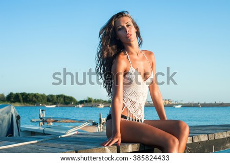 young woman enjoy in  summer sun at boat dock  at sea sunny summer day  - stock photo