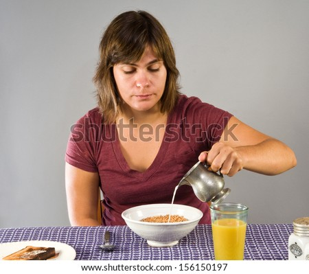 Young woman enjoying a gluten free breakfast - flax cereal and gluten-free bread - stock photo