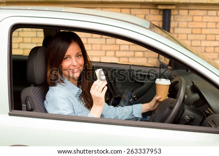 young woman enjoying a healthy snack and a cup of coffee in her car. - stock photo