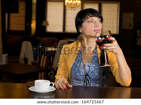 Young woman enjoying a large glass of red wine and cup of espresso coffee while sitting relaxing at a bar counter in a hotel or nightclub looking off to the side - stock photo