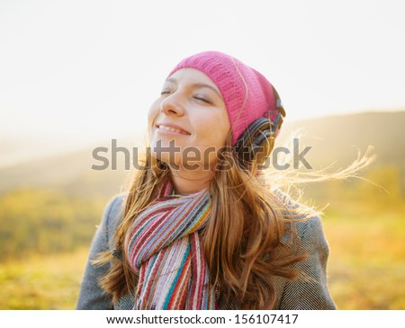 Young woman enjoying a music in the fall season. Autumn outdoor portrait. - stock photo