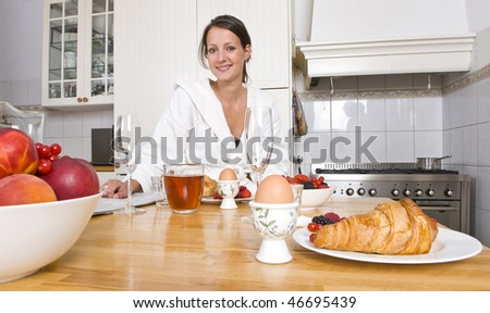 Young woman enjoying a rich breakfast at a kitchen counter with fruit, croissants, eggs, and the morning paper - stock photo