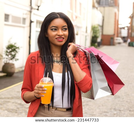 young woman enjoying a smoothie with shopping bags.  - stock photo