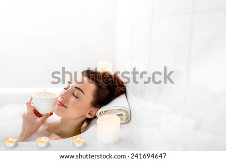 Young woman enjoying coffee while lying in the bath with foam and candles. General plan with space for text - stock photo