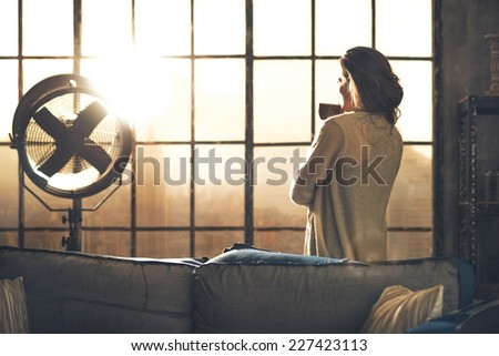 Young woman enjoying cup of coffee in loft apartment. rear view - stock photo