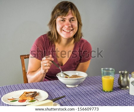 Young woman enjoying gluten-free breakfast - flax cereal and gluten free toast - stock photo