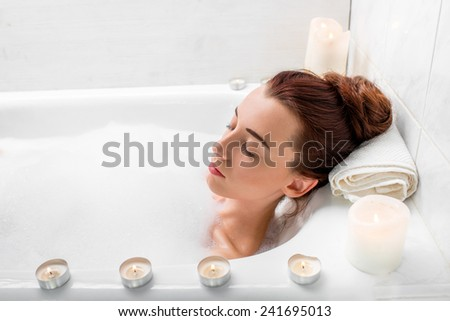 Young woman enjoying lying at the bath with foam and candles - stock photo