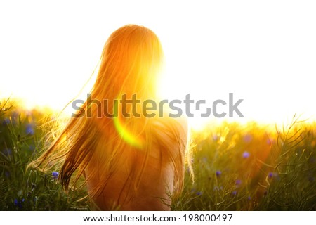 Young woman enjoying nature and sunlight in canola field - stock photo