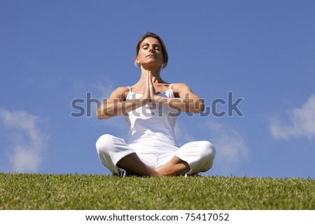 young woman enjoying nature in a yoga lotus pose - stock photo