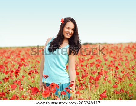 Young woman enjoying nature in spring poppy field - stock photo