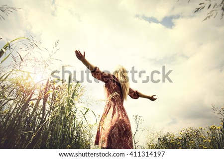 young woman enjoying nature in the middle of a meadow, welcome warm season - stock photo
