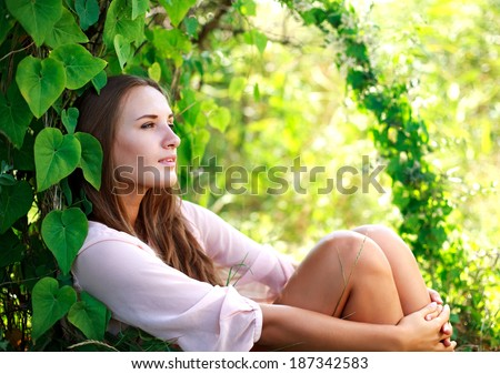 Young woman enjoying summer day in the green garden - stock photo