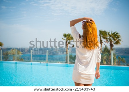 Young woman enjoying sun on sunbed at tourist resort - stock photo