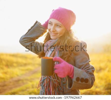 Young woman enjoying the fall season. Autumn outdoor portrait. - stock photo