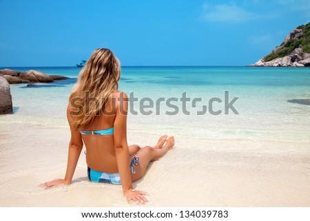 Young woman enjoying the sunshine on a tropical beach - stock photo