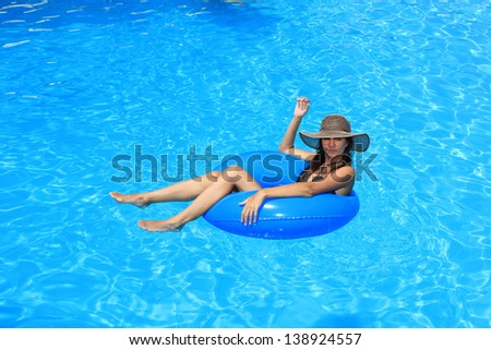 Young woman enjoying the swimming pool in the summertime - stock photo