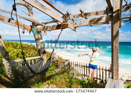 Young woman enjoying view of tropical beach on Eleuthera Bahamas - stock photo