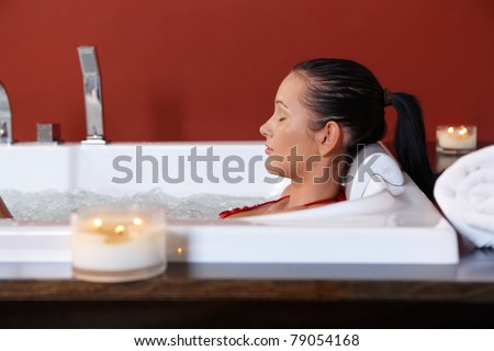 Young woman enjoying wellness bubble bath with eyes closed in candle light.? - stock photo