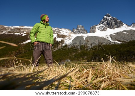 Young woman enjoys beautiful view into high mountains, Patagonia, South America - stock photo