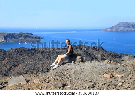 Young woman enjoys sea view sitting on a stone at volcano of Santorini - stock photo