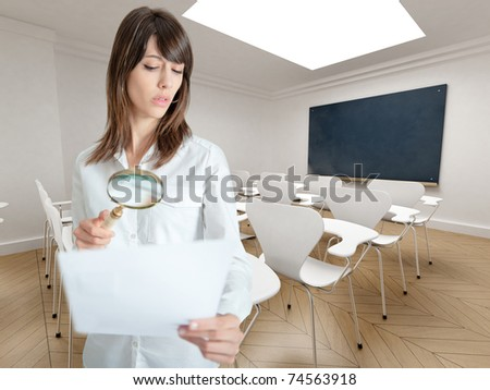 Young woman examining a paper through a magnifying glass in a seminar room - stock photo