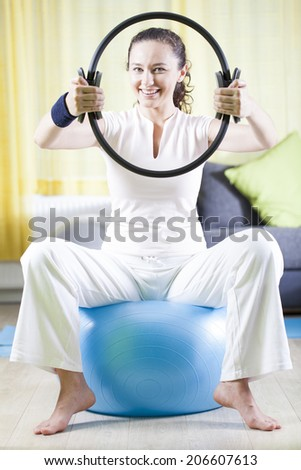Young Woman Exercise With Pilates Ring, Pressing it With Hands - stock photo