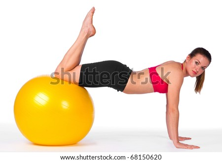 young woman exercise with yellow pilates ball - stock photo