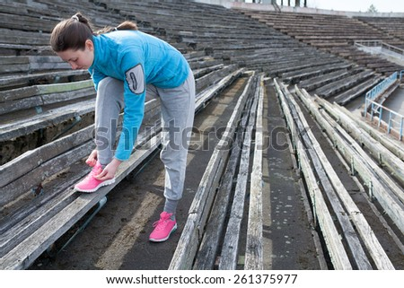young woman exercises jogging and running on athletic track on stadium on a track and among stadium rows - stock photo