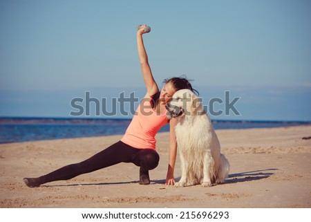 young woman exercises with her dog - stock photo