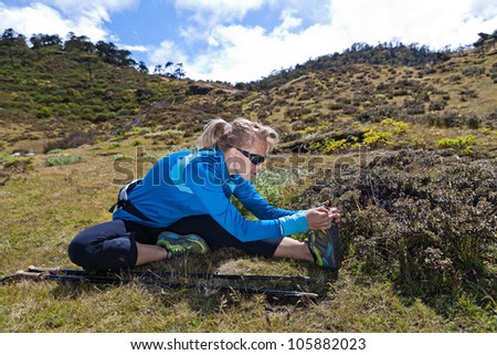 Young woman exercising and stretching in mountains, nordic walking in summer - stock photo