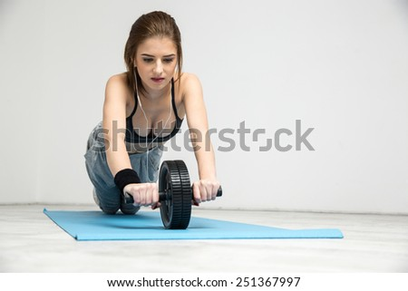 Young woman exercising fitness workout abdominal wheel - stock photo