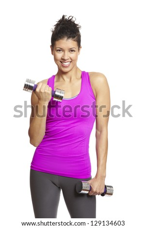 Young woman exercising in sports outfit holding dumbbells on white background - stock photo