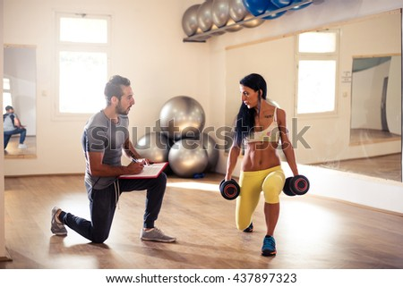 Young woman exercising in the gym with the help of personal trainer. - stock photo