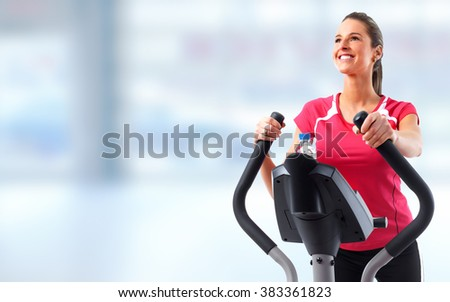 Young woman exercising on elliptical trainer. - stock photo