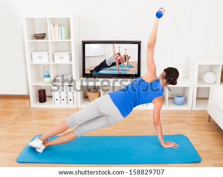 Young Woman Exercising On Mat In Front Of Television - stock photo
