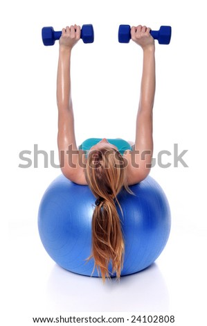 Young woman exercising with dumbbells laying on a fitness ball - stock photo