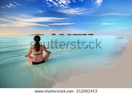 Young woman exercising yoga in turquoise lagoon with overwater bungalows around tropical island - stock photo