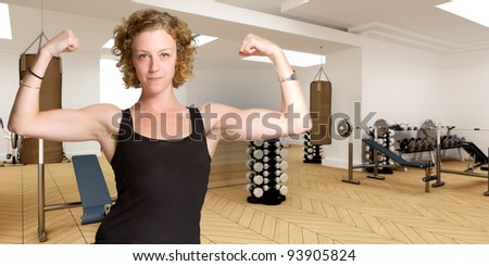 Young woman exhibiting her biceps in a gymnasium - stock photo