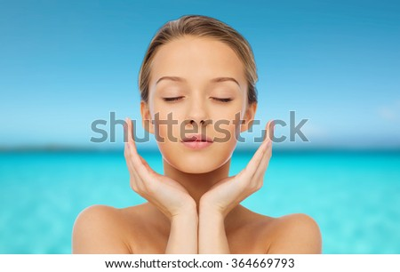 young woman face with hands over sea and sky - stock photo