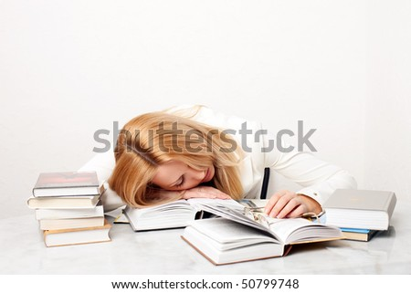 Young woman falling asleep while studying at the table with a lot of books - stock photo