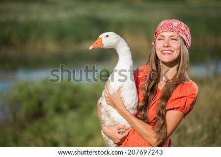 Young woman farmer holds goose happy smiling  - stock photo