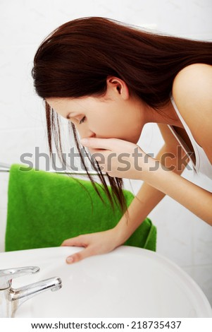 Young woman feeling sick in the bathroom. - stock photo