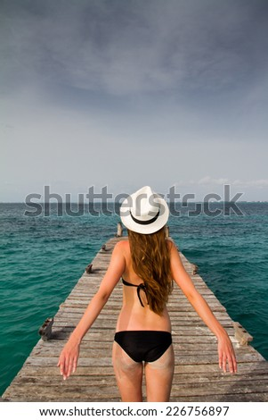 Young woman feeling the breeze at the sea wearing a black bikini and a white hat standing at the pier  - stock photo