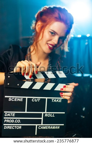 Young woman film director with clapper portrait. Blue light on background. Focus on clapper. - stock photo