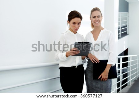 Young woman financier consulting with managing director about own work on digital tablet while standing in modern office interior, smiling female proud ceo posing while her colleague using touch pad - stock photo