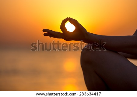 Young woman fingers in yogic Jnana mudra, close up, copy space. Relaxation, meditation on sea at sunset or sunrise - stock photo