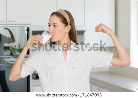 Young woman flexing muscles while drinking milk in the kitchen at home - stock photo