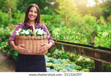 Young woman florist working outdoors at the nursery gathering flowers in a large wicker basket she is holding in her hands standing smiling at the camera, with copyspace - stock photo