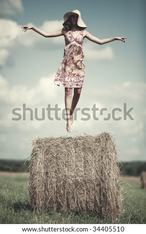 Young woman flying over haystack in a field. - stock photo